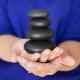 person holding hot stone massage stones